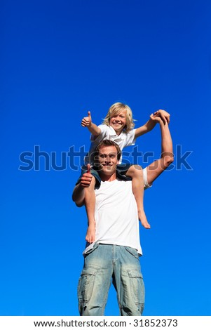 Smiling son on his father's shoulders with thumbs up - stock photo