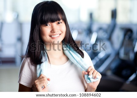 Smiling sport woman with towel looking at camera