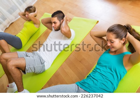 Smiling sportive adult people working out on mats in gym - stock photo