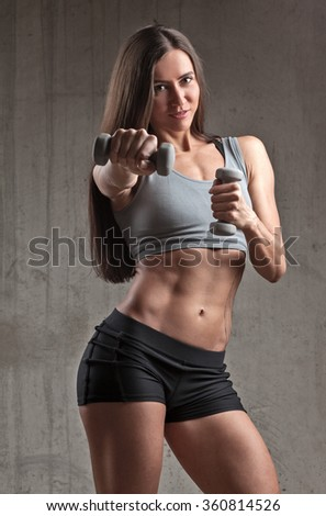 smiling sportswoman doing punch with dumbbell in brutal interior - stock photo