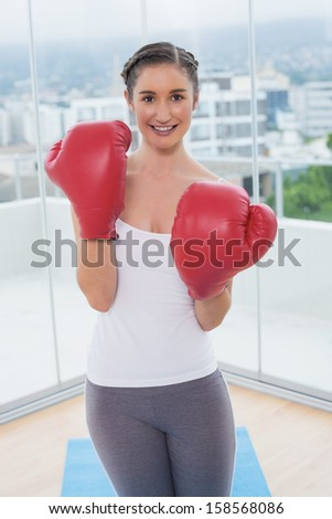 Smiling sporty brunette wearing red boxing gloves in bright fitness studio