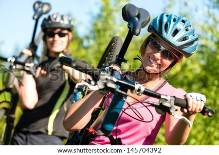 Smiling sporty couple carrying their mountain bikes - stock photo