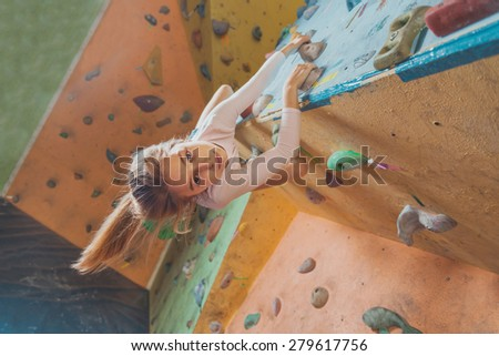 Smiling sporty little girl climbing artificial boulder on practical wall in gym - stock photo