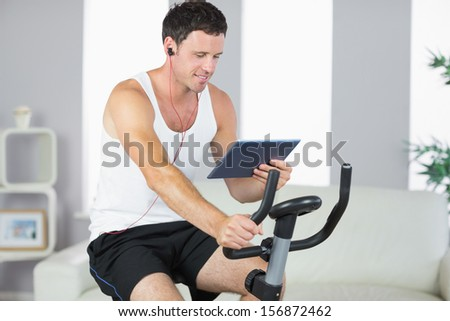 Smiling sporty man exercising on bike and using tablet in bright living room - stock photo