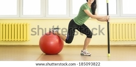 Smiling sporty slim sexy woman in sporty uniform crouches with fit bar and based leg on red rubbish fitball on yellow wall and windows background  - stock photo