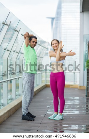Smiling sporty woman and man stretching hands