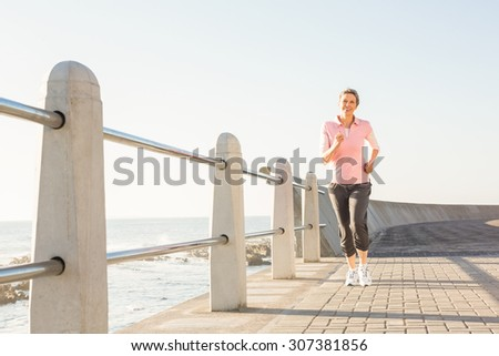 Smiling sporty woman jogging at promenade on a sunny day - stock photo