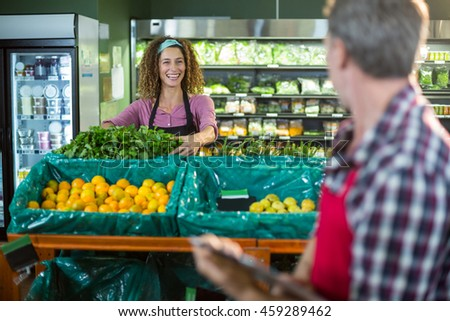Smiling staffs interacting with each other in organic section of supermarket - stock photo