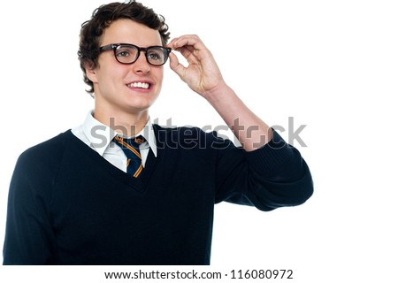 Smiling student adjusting his spectacles while looking far away - stock photo