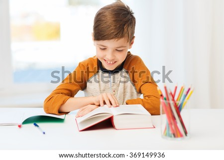 smiling, student boy reading book at home - stock photo