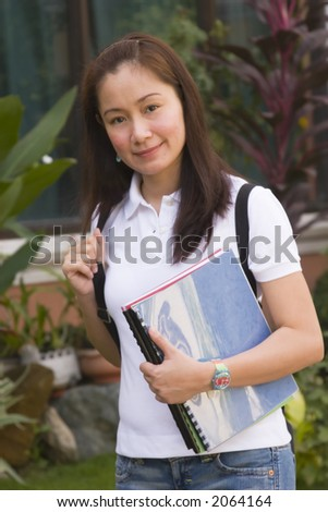 Smiling student carrying bag and books outdoors
