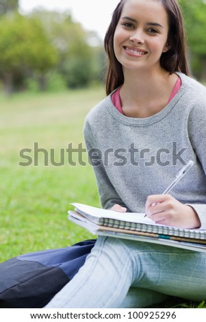 Smiling student doing her homework while sitting down in the countryside