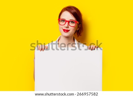 Smiling student girl in white shirt and glasses with white board on yellow background