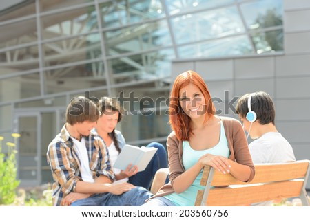 Smiling student girl with friends sitting bench outside college summer - stock photo