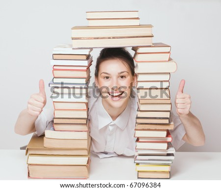 Smiling student girl with her books and thumb up fingers - stock photo