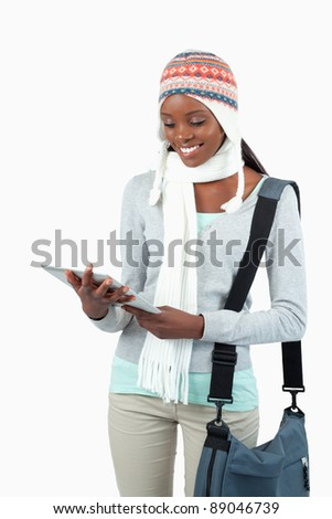 Smiling student in winter clothes with her tablet against a white background - stock photo