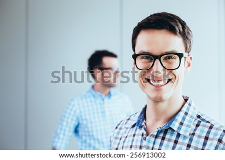 Smiling student looking at camera happily - stock photo