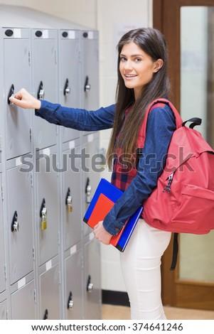 Smiling student opening locker at university - stock photo