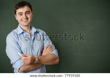 smiling student or teacher at the blackboard - stock photo