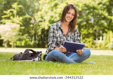 Smiling student sitting and using tablet pc in park at school