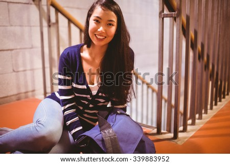 Smiling student sitting in hallway at the university