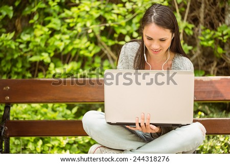 Smiling student sitting on bench listening music and using laptop in park at school - stock photo