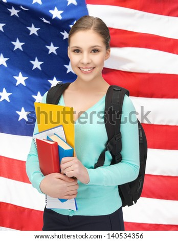 smiling student with books and schoolbag over american flag - stock photo