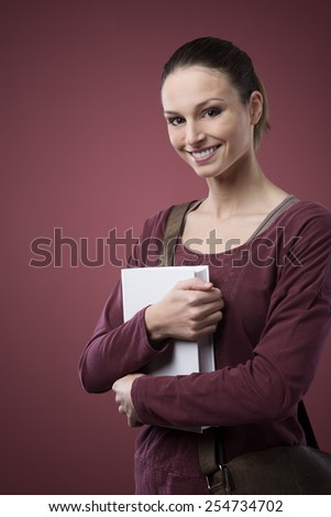 Smiling student with textbook and bag posing and looking at camera - stock photo