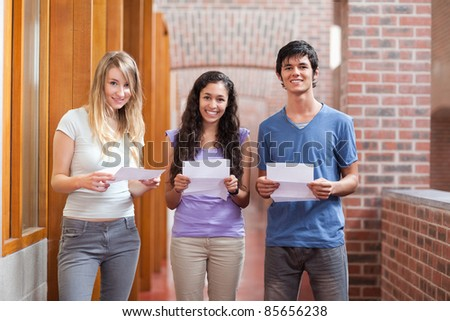Smiling students holding a piece of paper in a corridor - stock photo