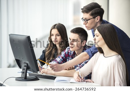 Smiling students looking at computer pc at college.