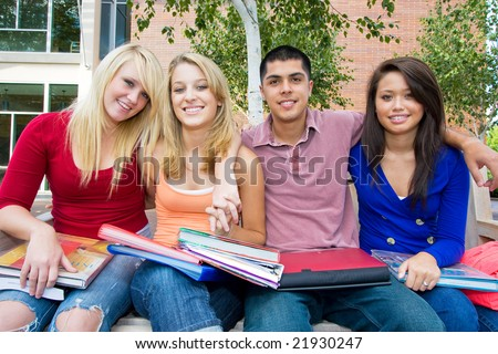 Smiling students sitting on a bench holding books outside of school. There are three girls and one guy, and he has his arms around them. Horizontally framed photo. - stock photo