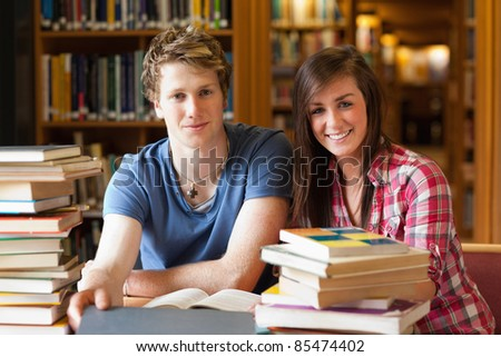 Smiling students surrounded by books in a library - stock photo
