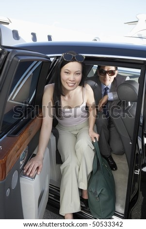 Smiling, Stylish Woman Getting Out of a Car with luggage - stock photo
