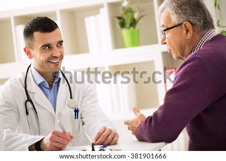 Smiling success doctor listening carefully his senior patient in office - stock photo