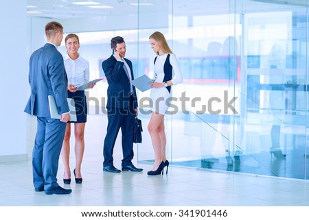Smiling successful business team standing in office - stock photo