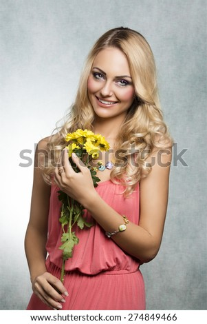 smiling summer girl , with blond hair and pink dress , she is looking in camera and keeping some yellow flowers - stock photo