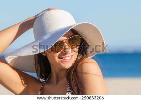 smiling summer woman on beach with sunglasses and floppy hat - stock photo