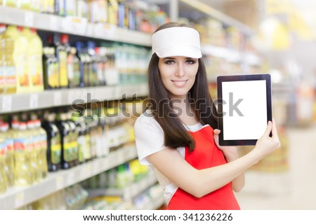 Smiling Supermarket Employee Holding a Pc Tablet - Portrait of a young sales clerk in a market store   - stock photo