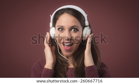 Smiling surprised woman with headphones listening to music - stock photo