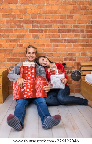 Smiling Sweet Young Couple Sitting on Floor Holding Christmas Gift Boxes. Leaning on Bricks Wall Background. - stock photo