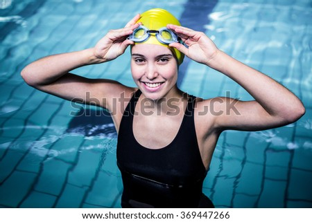Smiling swimmer woman holding her swimming glasses in swimming pool - stock photo