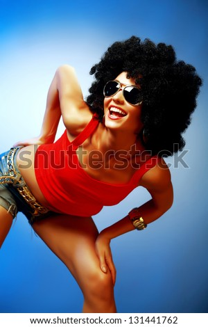 Smiling tanned woman with afro hair posing against blue background - stock photo