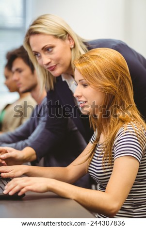 Smiling teacher explaining something to student in the computer room - stock photo