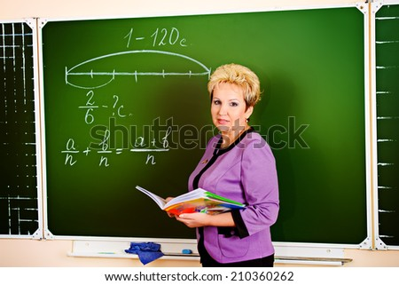 Smiling teacher giving a lesson at a classroom. Education. Occupations. - stock photo