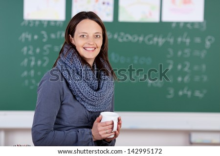 Smiling teacher having coffee inside the classroom