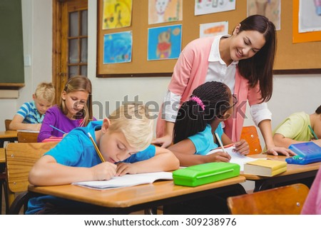 Smiling teacher helping a student at the elementary school - stock photo