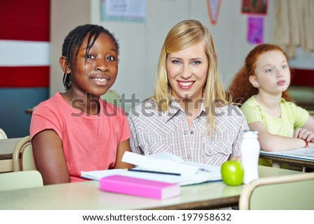 Smiling teacher helping african girl in elementary school class - stock photo
