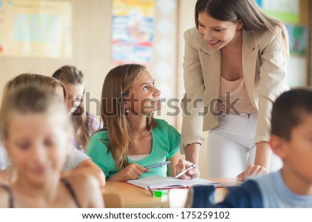Smiling teacher helping her students during the lesson. - stock photo