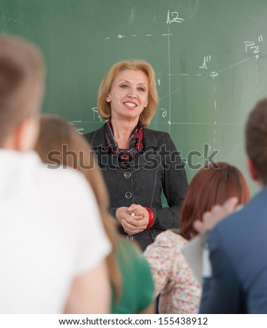 Smiling teacher on a blackboard listening to her students - stock photo