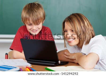Smiling teacher showing boy student a laptop - stock photo